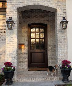 Entryway with limewash brick and Bevolo gas lamps