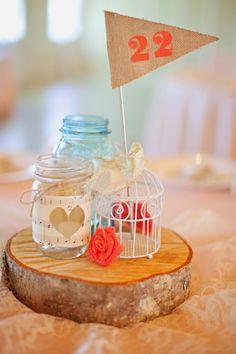 coral and blush barn wedding Salem Oregon twinkle lights wood round centerpiece blue mason jar and bird cage