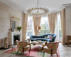 In the living room of a London townhouse, neutral curtains add a bout of English elegance to the space, which is furnished with a vintage sofa by Ico Parisi and Otto Schultz chairs covered in a Clarence House fabric. The light fixture is by Vilhelm Lauritzen.