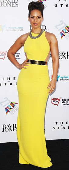 Alicia Keys attends in the 27th ARIA Awards in a bold, bright yellow gown by Stella McCartney paired with a gold cuffed belt and elaborate, linked necklace.
