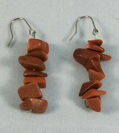 These are beautiful earrings with Gold-stone pieces in a line. These earrings measure at 3 cm.