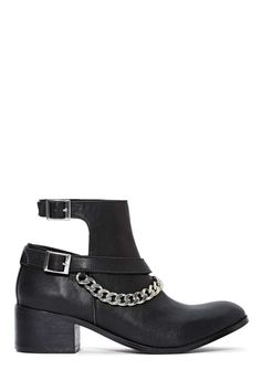 Unleash your inner shoe freak with Shoe Cult! These black faux leather ankle boots have two adjustable silver buckle closures at side above cutouts and silver chained detailing.