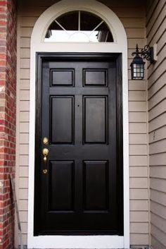 Black front door in white frame
