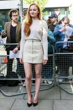 Sophie Turner usa look com tons neutros, combinando mini saia com zíper, tricot e scarpin preto.