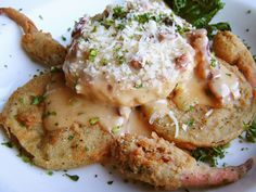 Original Oyster House Crab Stack - A delicious grilled lump crab cake stacked on top of thick cut fried green tomatoes finished with tasty Tasso ham cream sauce.