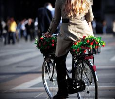 Blonde girl rides her flower-laden bicycle with fenders in the Piazza Duomo - Check out Bicycles of Italy story by Patty Mooney at http://sandiegovideoproduction.com/bicycles-of-italy/