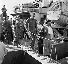 A black and white photograph showing wounded British soldiers disembarking from a warship