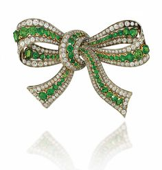 A DEMANTOID GARNET AND DIAMOND BROOCH. Modelled as a bow, set with a central line of graduated oval-cut demantoid garnets within an old-cut diamond border, mounted in silver and gold, circa 1935, 7.5cm wide
