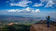 A tourist takes a photo at the top of Pikes Peak mountain in the Front Range of the Rocky Mountains within Pike National Forest, 10 miles of Colorado Springs, Colo. A designated National Historic Landmark, Pikes Peaks rises to 14,115 feet and is one of Colorado's 54 fourteeners, mountains that rise more than 14,000 feet. (JOE KLAMAR/AFP/Getty Images)