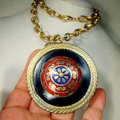 Large Thrones Game Medallion 1960s, Enamel Round Pendant on Chunky Gold Chain, Military Shield Necklace, Crusaders, Knights, Royal Orders Dramatic mandala Shield medallion for any Day , for Military, Royalty or CRUSADER moments The striking round gold pendnat has red and blue cloisonne design surrounded by black enamel and a gold frame This pendant is 2 5/8 across ( 6.76cm ) The thick and bright shiny gold metal chain is 30 ( 76.2cm ) long but you can hook it as short as you like The chain…