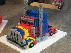 All buttercream Optimus Prime semi, for cousins birthday. Stacks are pretzel rods covered in butter cream. I used a 1/2 sheet cake and then divided it in 3rds, used two of the thirds stacked and other two I cut in 1/2 again and made two small square cakes with transformers logos... Kids loved it all. Biggest mistake was trying to fill the cake and then carve it.. I had minor leakage but used stiff frosting as a morter!!!
