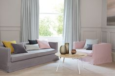 カーテンが3人掛けソファや壁と、ほぼ似たような色合いでコーディネートしている例。ピンクのソファやクッション、ローテーブルの小物が引き立つインテリアとなっています。