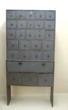 """PAINTED APOTHACARY CUPBOARD. Stamped """"Weeks & Gilson"""" on drawer fronts. Weeks and Gilson Glass Works, 1850-1873, Stoddar, New Hampshire. Pine with old blue grey paint, nail construction and twenty-seven drawers. 12""""d. 36""""w. 75 1/2""""h."""