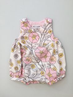 Baby girls romper - size 0 to 3 months  + This stunning romper is made from a lovely vintage cotton. It has a roomy bubble design, cute decorative front pocket, and is fastened by easy access plastic snaps fixed on the crotch and shoulders.  + This particular fabric, I bought as part of a vintage bedding set, in perfect condition, so its very special. The grey in the pattern seems to bring through a modern feel too, which I love.  + I recommend machine washing at 30 degrees, to help the…