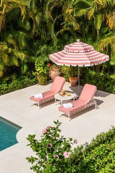 cool vintage pink chaise lounges and pink and white stripe sun umbrella by the pool.