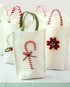 Gift Bags with a Twist. make simple felt sacks (sew side seams, fold bottom corners toward the center, tack with thread). embellish with rickrack handles and a bright ornament. the sturdy grips are nothing more than two lengths of intertwined trim. Christmas Sewing, Noel Christmas, Christmas Gift Wrapping, Handmade Christmas, Christmas Ornaments, Christmas Bags, Christmas Projects, Holiday Crafts, Holiday Fun