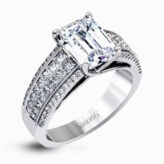 This eye-catching contemporary white gold engagement ring features a dazzling setting with .19 ctw of round cut white diamonds and .75 ctw of princess cut diamonds.