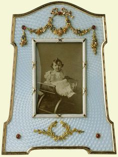 Fabergé frame containing a photograph of Tsarevitch Alexei. This silver-gilt frame is enamelled in pale blue guilloché in a geometric design and applied with ribbon-tied floral swags and a laurel wreath in four-colour gold set with cabochon rubies. Mark of Viktor Aarne, c. 1905. Bought by Tsar Nicholas II and Tsarina Alexandra Feodorovna, 21 June 1906 (165 roubles).