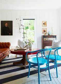 A bright space with a cottage feel gets a double dose of tension: bright blue chairs and a striped rug laid at an unexpected angle.