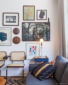Além de peças lindas de design, essa sala tem uma parede galeria com quadros e peças étnicas.