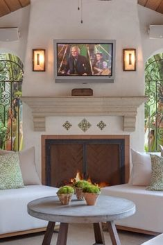 This stunning covered patio idea has a boho deco aesthetic. The tall cathedral ceiling above the white cushioned chairs are warmed by the large stone beige fireplace with a wall-mounted TV above it. #PatioIdeas #PatioDesign #PatioDecoratingIdeas #CoveredPatio  Courtesy of TopTenRealEstateDeals.com Rustic Wooden Bench, Wooden Dining Tables, Room Design Software, Tv Wall Design, Safe Room, Home Room Design, Wooden Ceilings, Spacious Living Room, Beige Walls