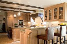 I like the dark ceiling beams, carved hood and thick glass pendants.  I do not like cabinet color or style.