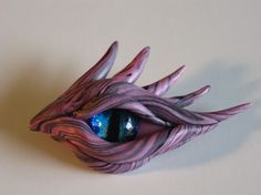 The Dragon Eye Myth comes from the end of the dragon age.  The eye is watching for the pending signs of the new age of wisdom. The structure of each is hand sculpted from cernit.  Eye irises are hand painted by the artist. Each piece is an original one-of-a-kind work of art.