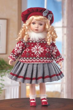 Nordic Natalie is dressed for the chilly weather in a faux fur neck warmer, a Nordic-style sweater, gray skirt with a red stripe and a matching hat. She features curly blond hair, porcelain head, hands and feet.