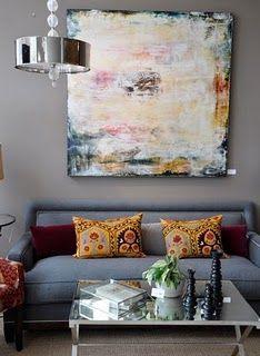 grey wall, awesome painting. Suzani pillows.