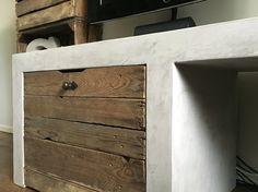 Een tv meubel met beton look en een kastje van oud fruitkistjes hout.