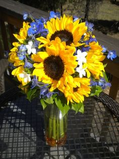 Bridal bouquet with yellow sunflowers, blue delphinium and white stephanotis by Glamorous Occasions in Flagstaff, AZ.