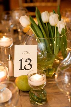 White tulip wedding centerpieces and table numbers tucked in moss spheres #MarieeAmi #Weddings #ArdenPhotography