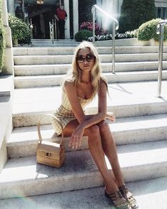 straps sandals purse striped yellow dress stairs rails bushes sunlight sun glasses