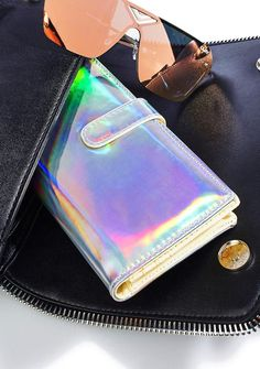 Neu Currency Holographic Wallet ...no, we cannot give U change for space money! Take yer business to tha star with this sikk wallet, featurin' an insanely bright silver holographic construction, foldover style with magnetic closure, and plenty of slots fer yer cards 'N ca$h.