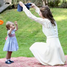Captivated by her mother, 16-month-old Princess Charlotte looks up as her cardigan is whipped off with a flourish