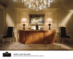 CREAM HALLWAY Inner hall with classic cream and gold leaf detailing, wall panelling, curved sideboard with burr oak inlay and gadrooning, high-back Empire chairs upholstered in black velvet.