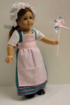 Felicity™ is all ready to go to the Town Fair. Her Teal dress is trimmed with 3 rows of ribbon, and has white sleeves, that match her white mop cap. Cover it up with a pink striped apron. Black socks and black shoes finish her outfit, and she can carry a pinwheel that she gets at the fair. Handmade in my smoke free home. Doll and stand not included. Prairie Wind Girl is not affiliated with American Girl® or Mattel®. No Endorsement is implied.