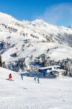 Skiers and snowboarders on the slopes of winter ski resort St. Anton, Austria.