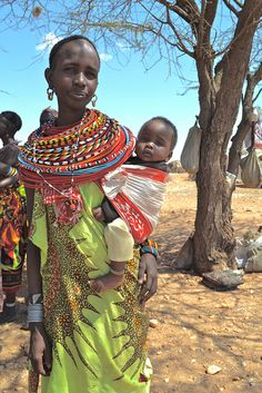 Samburu mother carries her baby in a sling on her side or on her back while still building the tribes homes, fetching water, cooking and cleaning.