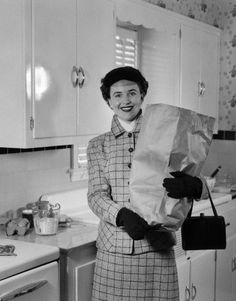 1950s smiling woman in kitchen holding grocery bag handbag wearing hat gloves looking at camera
