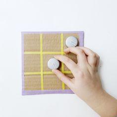 ¿Cuál es vuestro juego clásico favorito? #DIY Tres en raya con cartón reciclado ⭕ ✖️ . ¡10 minutos de reloj y con materiales que seguro que tienes en casa! . MATERIALES: . Un trozo de cartón algo grueso de 15x15 centímetros, 10 tapones de refresco, cúter y  Washi tape de colores , uno fino y otro de tamaño normal (15mm) . CÓMO HACERLO: . 1) Prepara una pieza de cartón algo grueso de 15 x 15 centímetros. 2) Marca con un lápiz a los 5 y a los 10 centímetros. Con un washi tape fino… Washi, Diy, Board Games, Recycling, Handmade, Manualidades, Hipster Stuff, Bricolage, Handyman Projects