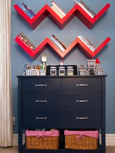 Bright red floating wall shelves add a chevron effect to the blue wall in this kid's room. A dark blue dresser sits below, offering plenty of storage space via drawers and two wicker baskets.