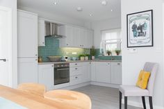 Natural wood furniture contrasts with the simple grey tones of the kitchen. This…