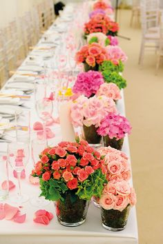 The marquee was dressed with white and cream drapes and chandeliers; the tables were decorated with scattered rose petals and featured low floral displays