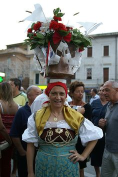 Festa Di San Rocco  Orsogna Italy  ~ Women with Conga - used long ago to carry water home. The women is dressing in traditional Abruzzo costume. During the feast. They walk around town with the conga's on their heads. Circle- is indicative of Orsonga and the triangular is indicative or Abruzzo