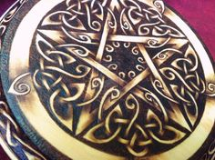 """This pentacle is a One of a Kind design hand pyrographed on a 7-inch (17.8cm), solid wood plaque. As always, it was burned entirely by hand, without the use of a router or laser-etching machine. The design was created the """"old fashioned"""" way, with pencil, eraser, and lots of patience, and the burning was done layer by layer to give beautiful gradations of tone and shade."""