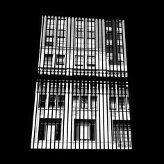 A view of the building on the other side of the street through a grilled window framed in black shadow. Undated, Chicago, IL