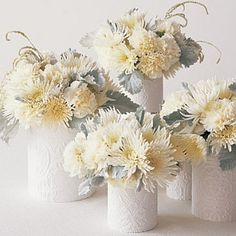 wrap clean empty tin cans with embossed wall paper and re-purpose as chic vases for a fresh floral centerpiece