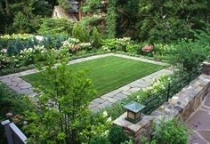 This grass lawn is bordered with irregular flagstone. A mixture of evergreens and flowers grow along the perimeter.
