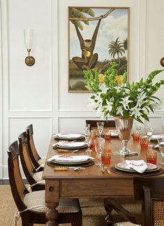 Teak-and-cane chairs surround an old harvest table in this old-meets-new dining room - Traditional Home® / Photo: Tria Giovan / Design: Ken Gemes